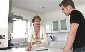 Грудастая зрелая шлюшка соблазнена возбужденным пасынком, и шлюшка не может устоять перед соблазном побаловать ее горячую сочную киску и трахается на кухне.