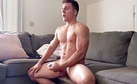 Biely svalnatý muž sediaci na pohovke dosahuje silný orgazmus a veľa semena dosahuje seba-láskou (prečítajte si masturbáciu)