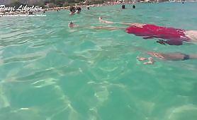 La caliente MILF húngara Puszi Likorlova, vestida con un sexy bikini en una playa pública, le hace una paja al gordo desconocido haciéndolo correrse. Sexo bajo el agua en la playa