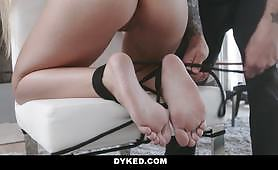 A tattooed mom finds a young lady tied to a chair, and then she fucks her pussy with a strap-on. She sucks her on different positions.